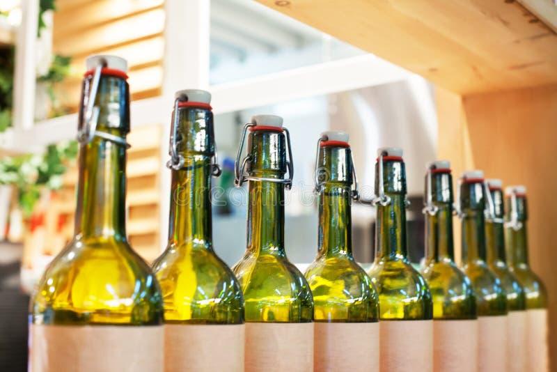 Zielone szklane butelki wino w linii na drewnianej półce, prętowa wewnętrznego projekta wytwórnia win produkcja, zamazany tło zam zdjęcia stock
