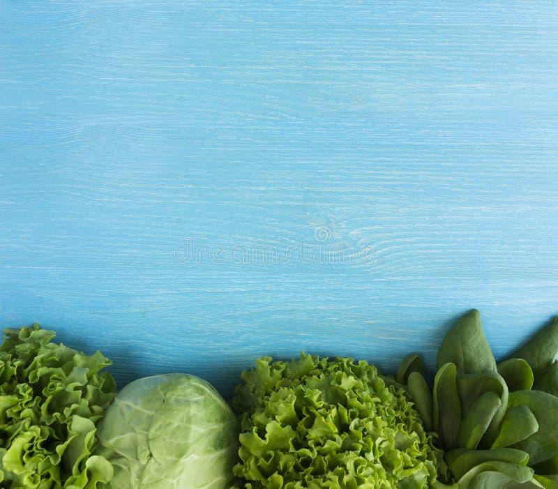 zielone warzywa Zielony warzywo na błękitnym drewnianym tle Szpinak, sałata i kapusta, Odgórny widok Warzywa przy granicą wizerun zdjęcia royalty free