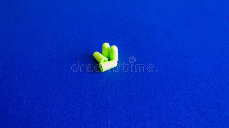 Zielone zatyczki do uszu na b??kitnym tle - wizerunek fotografia stock
