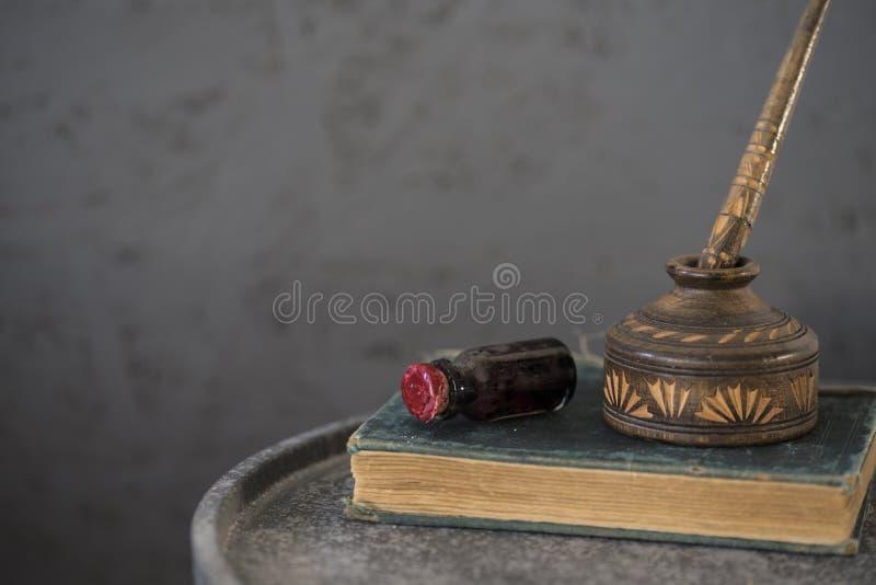 Zielonego szkła atramentu garnek i drewniany atrament puszkujemy z piórem, na starej książce, przeciw popielatemu tłu Przestrzeń  fotografia stock