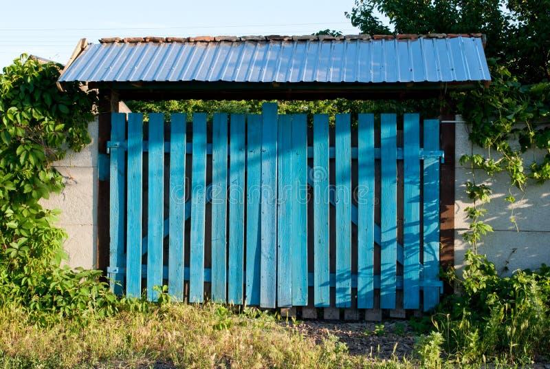 Zielonej drewnianej bramy furty wejściowy ogrodzenie, dach z dachówkowym dachem, liście wspinaczkowa roślina bluszcz, trawa fotografia royalty free