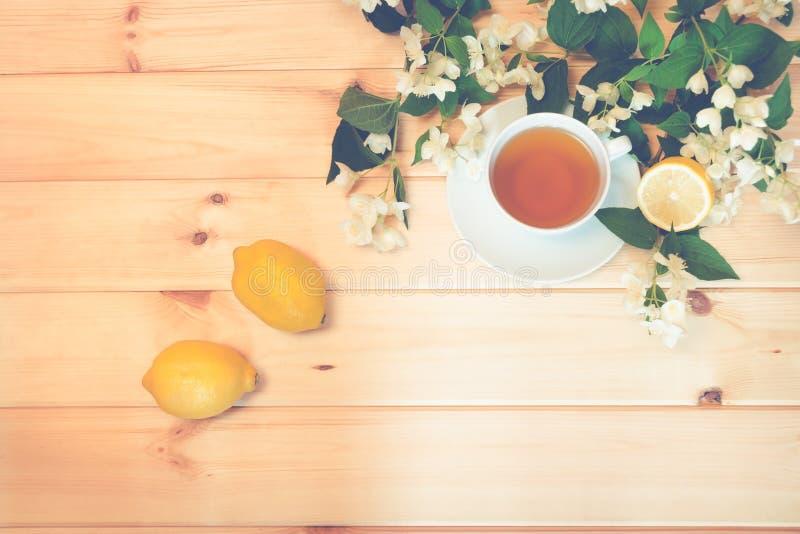 Zielonej herbaty, cytryny i jaśminu kwiaty na drewnianym tle, fotografia stock