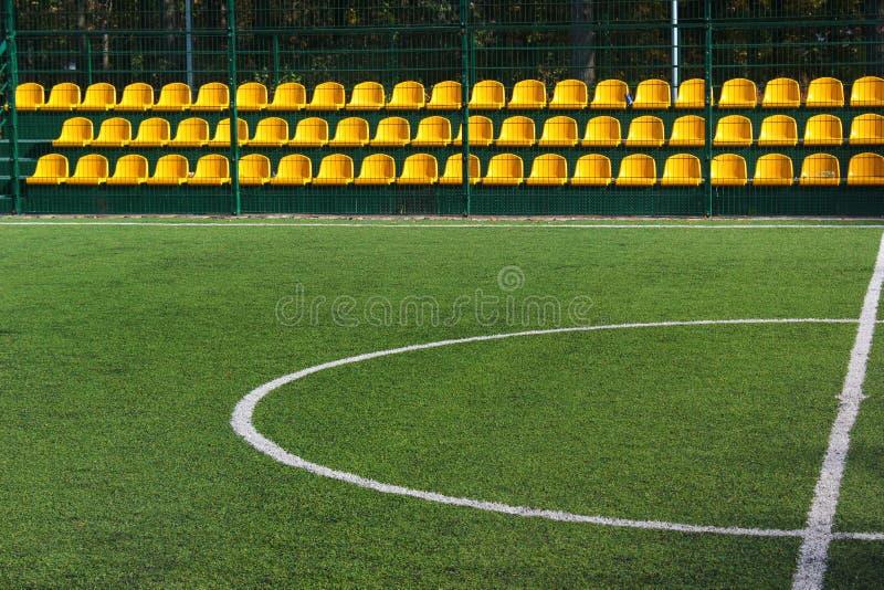 Zielonej trawy i koloru żółtego siedzenia przy pustym mini stadium piłkarski obraz stock