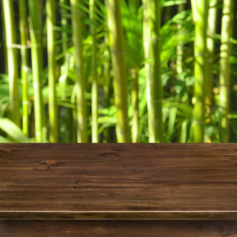 Zielony bambusowy gaju tło z drewnianym stołem zdjęcie stock