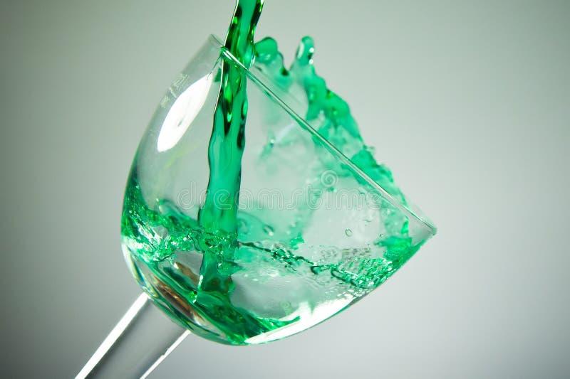 Zielony ciekły puring wewnątrz szkło zdjęcia stock