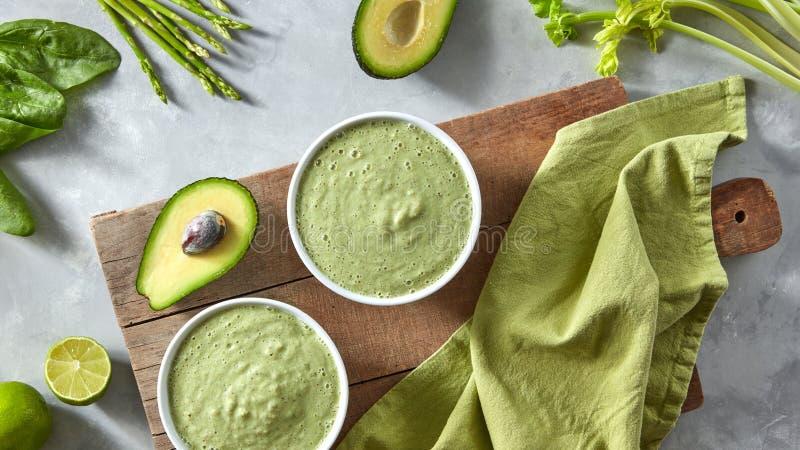 Zielony detox smoothie z avocado i asparagusem w bielu rzuca kulą na drewnianej desce z zieloną pieluchą na szarość kamieniu zdjęcie royalty free