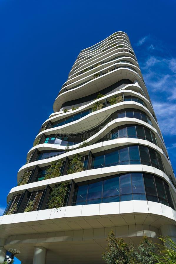 Zielony drapacza chmur budynek z curvy formami gr organicznie roślinami i zdjęcie royalty free
