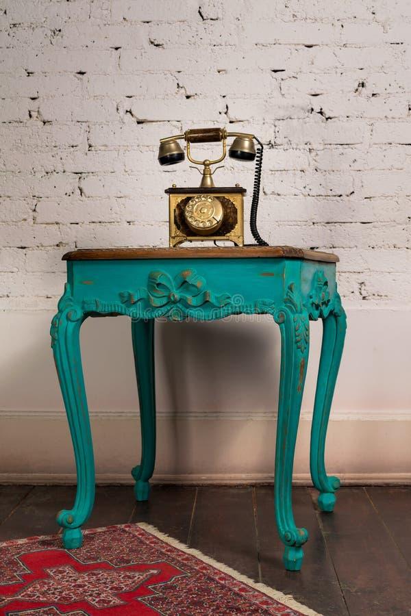Zielony drewniany stół i stary złoty zestaw telefoniczny zdjęcie royalty free