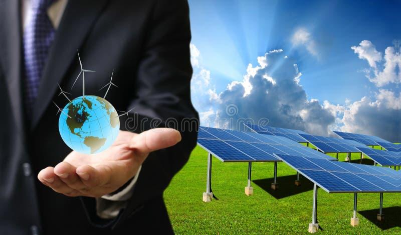 Zielony energetyczny pojęcie, biznesmen niesie świat silnik wiatrowy zdjęcie royalty free