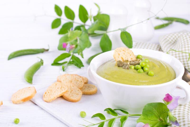 Zielony grochowej polewki puree z croutons w czarnym pucharze Na biel zdjęcie stock