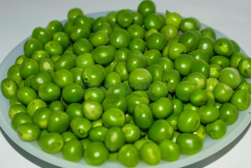Zielony grochowy str?k, zieleni grochy w bia?ym pucharze zdjęcia royalty free