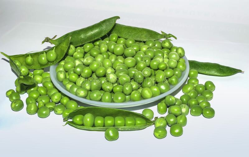 Zielony grochowy str?k, zieleni grochy w bia?ym pucharze zdjęcie royalty free