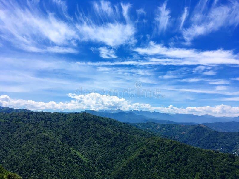 Zielony halny łańcuch pod niebieskim niebem fotografia stock