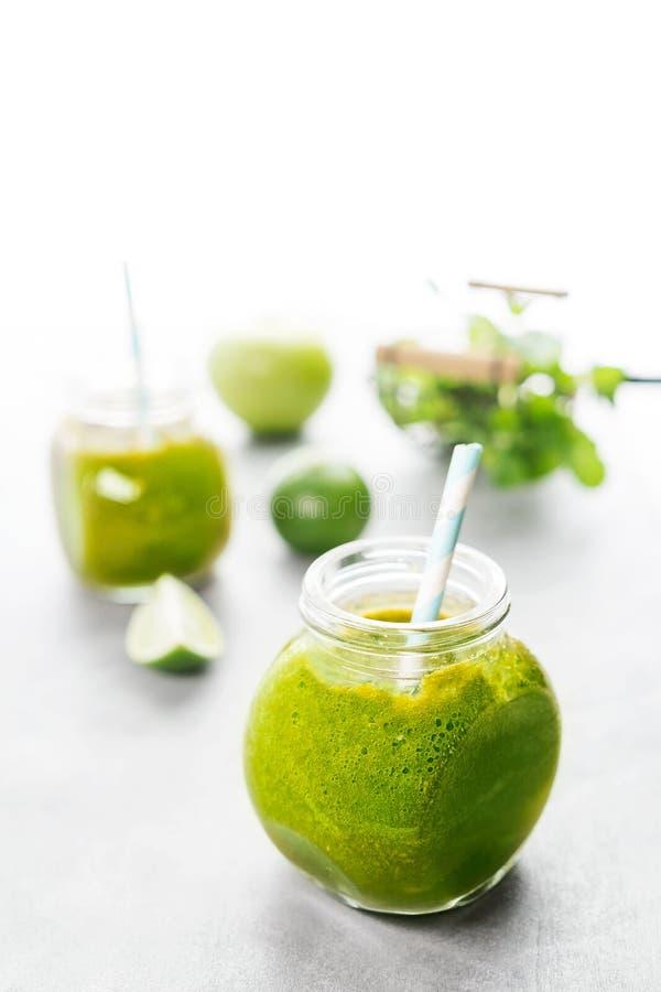 Zielony healty napój w dwa kamieniarzów słojach z zielonym jabłkiem, mennicą i wapnem na białym tle, Jarski karmowy pojęcie detox zdjęcia royalty free