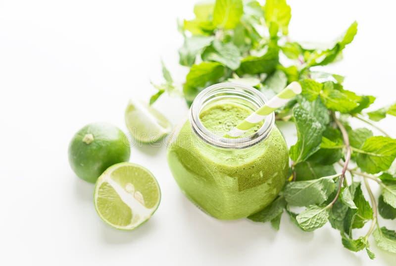 Zielony healty napój w kamieniarza słoju z zieloną świeżą mennicą i wapnem na białym tle Jarski karmowy pojęcie detoxification obrazy stock