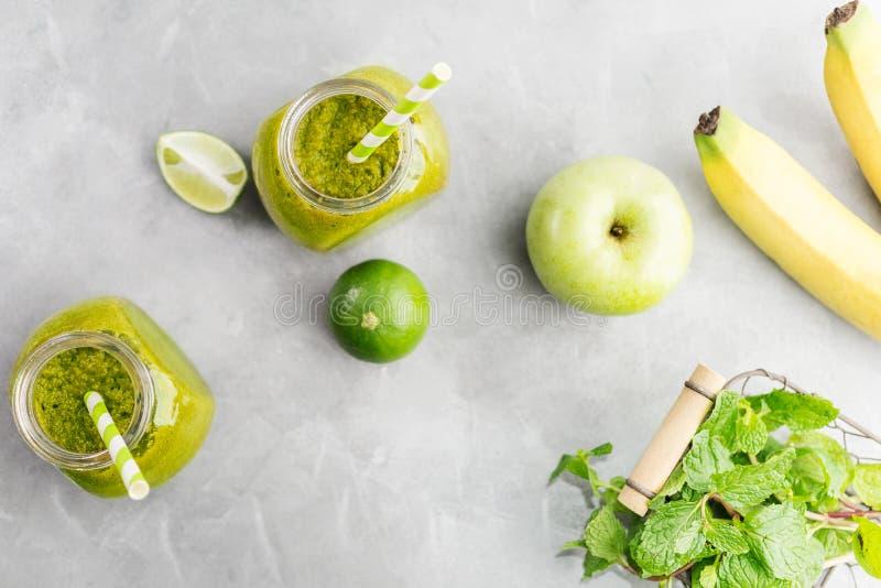 Zielony healty napój w kamieniarza słoju z zielonym jabłkiem, mennicą i wapnem na jaskrawym popielatym tle, Jarski karmowy pojęci obrazy royalty free
