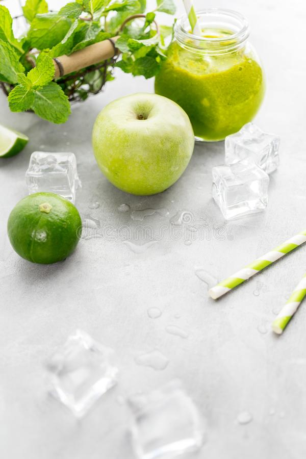 Zielony healty napój w kamieniarza słoju z zielonym jabłkiem, mennicą, wapnem i roztapiającymi kostkami lodu na popielatym tle, J obraz stock