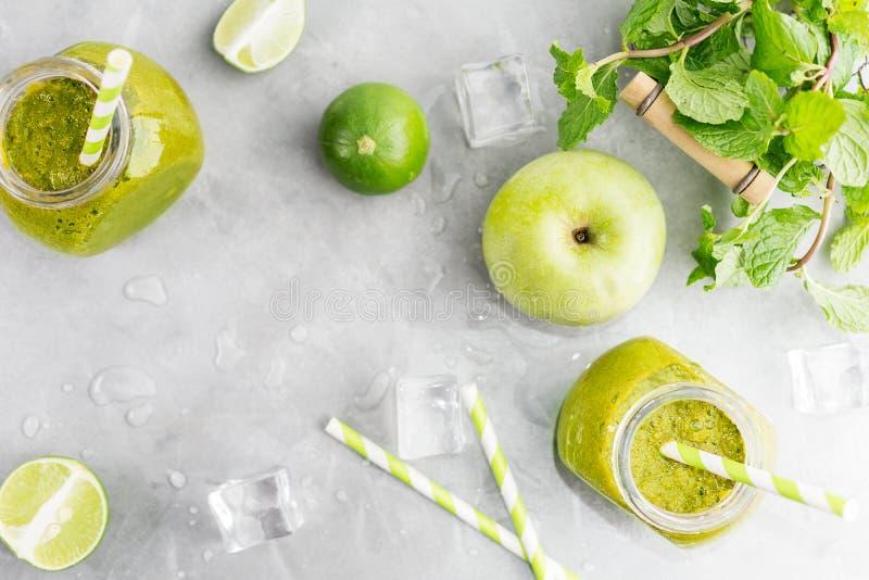 Zielony healty napój w kamieniarza słoju z zielonym jabłkiem, mennicą, wapnem i roztapiającymi kostkami lodu na popielatym tle, J zdjęcie stock