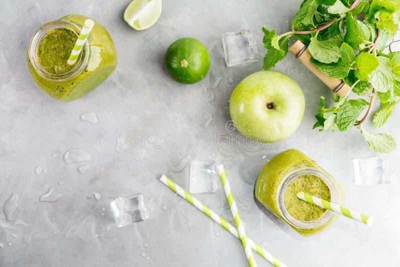 Zielony healty napój w kamieniarza słoju z zielonym jabłkiem, mennicą, wapnem i roztapiającymi kostkami lodu na popielatym tle, J fotografia royalty free
