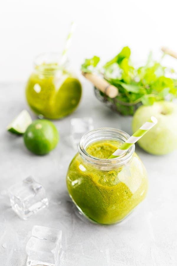 Zielony healty napój w kamieniarza słoju z zielonym jabłkiem, mennicą, wapnem i roztapiającymi kostkami lodu na popielatym tle, J obrazy stock