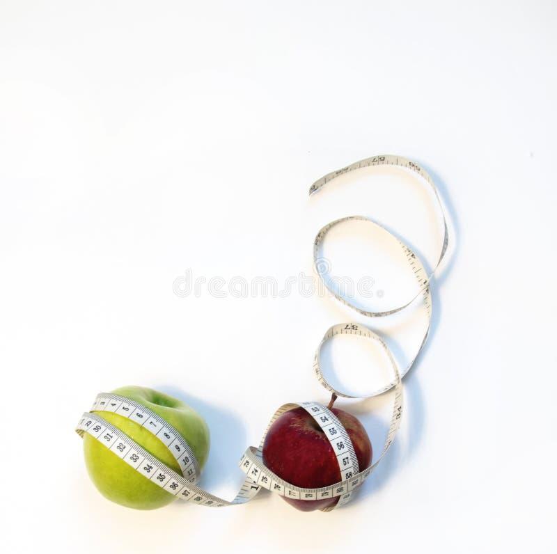 Zielony i czerwony jabłko zawijający w pomiarowej taśmie zdjęcie stock