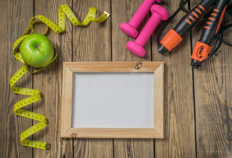 Zielony jabłko z pomiarową taśmą na drewnianym tle Jabłka i taśmy miara na drewnianym tle Gubić ciężar i jeść depresję obrazy royalty free