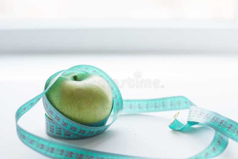 Zielony jabłko z pomiarową taśmą odizolowywającą na białym tle pojęcie diety miejsce tekst zdjęcie royalty free