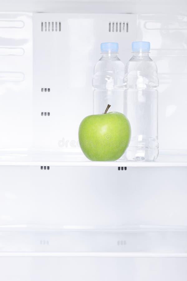 Zielony jabłko i butelki woda w fridge zdjęcia royalty free