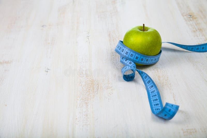 Zielony jabłko i pomiarowa taśma na drewnianym stole Pojęcie kostka do gry zdjęcia stock