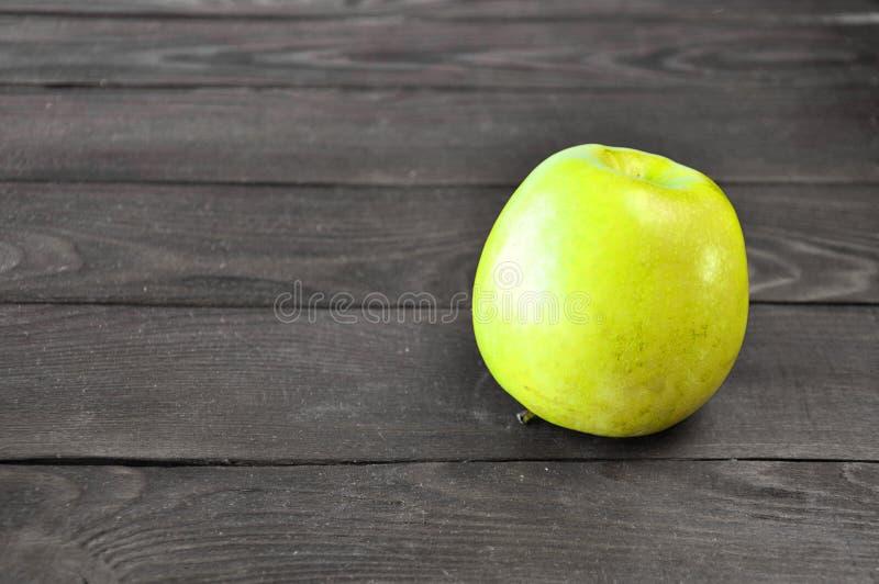 Zielony jabłko kłama na drewnianym stole fotografia stock