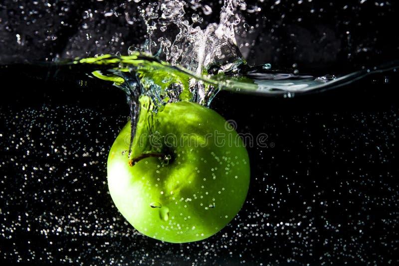 Zielony jabłko spada wewnątrz woda obrazy royalty free