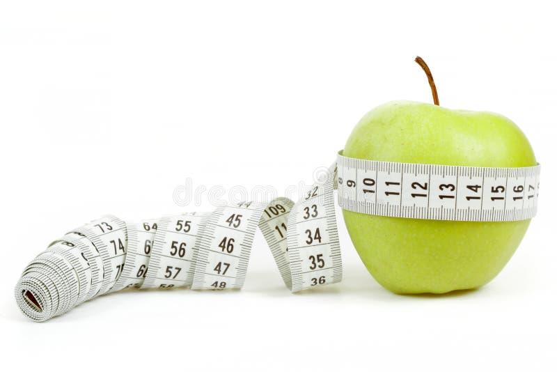 Zielony jabłko z pomiarowym taśmy i serca symbolem odizolowywającym zdjęcia stock