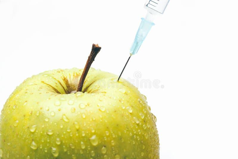 Zielony jabłko z strzykawką odizolowywającą zdjęcie royalty free