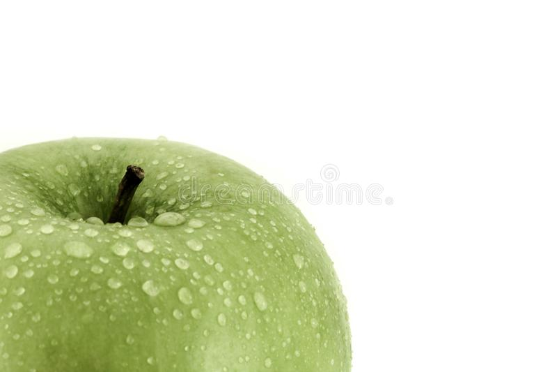 Zielony jabłko z wodnych kropelek zakończenia strzałem na bielu z kopii przestrzenią dla teksta obrazy royalty free