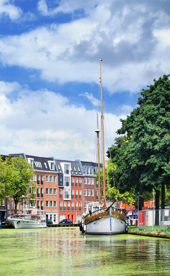 Zielony kanał z jachtami i budynkami mieszkaniowymi, Gouda, holandie zdjęcie royalty free