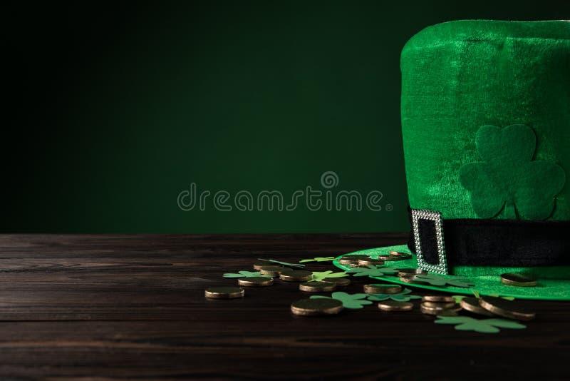 Zielony kapelusz z złotymi monetami i shamrock na drewnianym stole zdjęcie stock