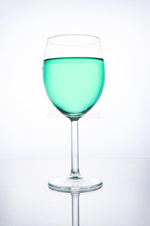 Zielony koktajl w szkle na białym tle z odbiciem obraz stock