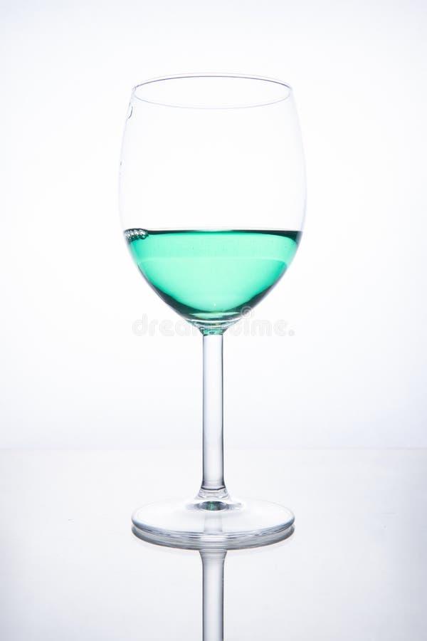 Zielony koktajl w szkle na białym tle z odbiciem zdjęcia stock