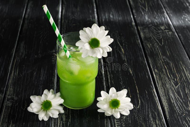 Zielony koktajl z pasiastymi słoma dekoruje z białymi kwiatami Kiwi sok z lodem na drewnianym czerń stole Miejsce dla twój zdjęcia stock