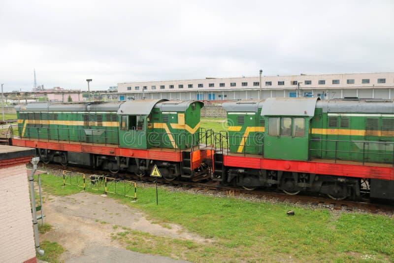 Zielony kruszcowy żelazo toczył pociąg towarowego, lokomotywa dla frachtu towary na poręczach przy stacją kolejową obraz royalty free