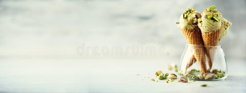 Zielony lody w gofra rożku z czekoladowymi i pistacjowymi dokrętkami na popielatym kamiennym tle Lata karmowy pojęcie, kopia zdjęcie stock