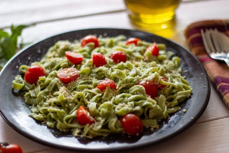 Zielony makaron z pomidorami i parmesan serem Biały tło zdjęcie stock