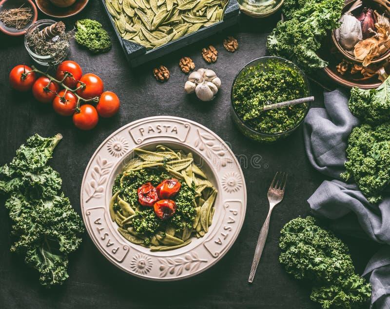 Zielony makaron z surowym kale pesto i piec na grillu pomidorami w talerzu z rozwidleniem na kuchennym stole z składnikami Wegani zdjęcie stock