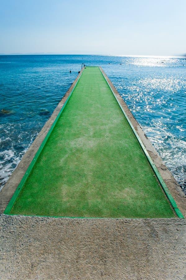 Zielony molo betonu molo nad błękitnymi wodami, molo z zielonym dywanem fotografia stock