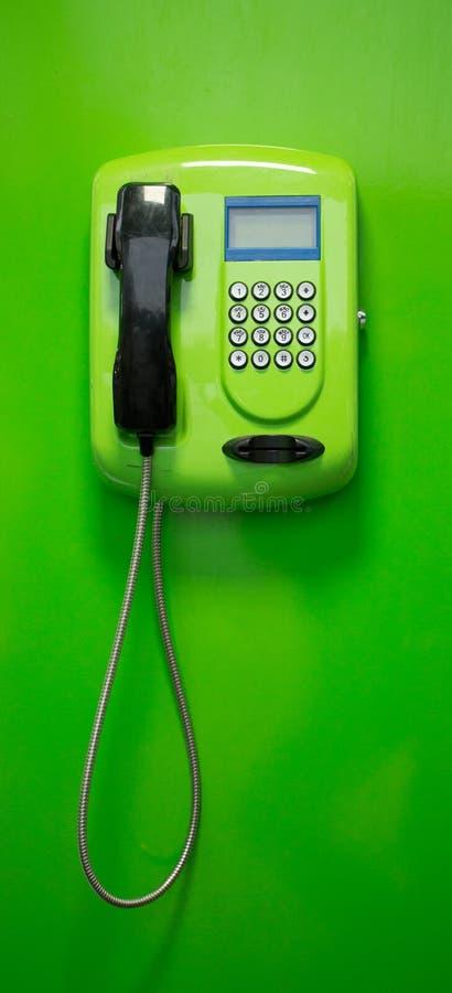 Zielony payphone z czarną tubką błękitnym pokazem i fotografia royalty free