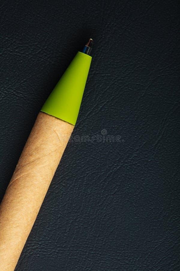 Zielony pióra writing materiał na czarnym rzemiennym tle zdjęcia stock