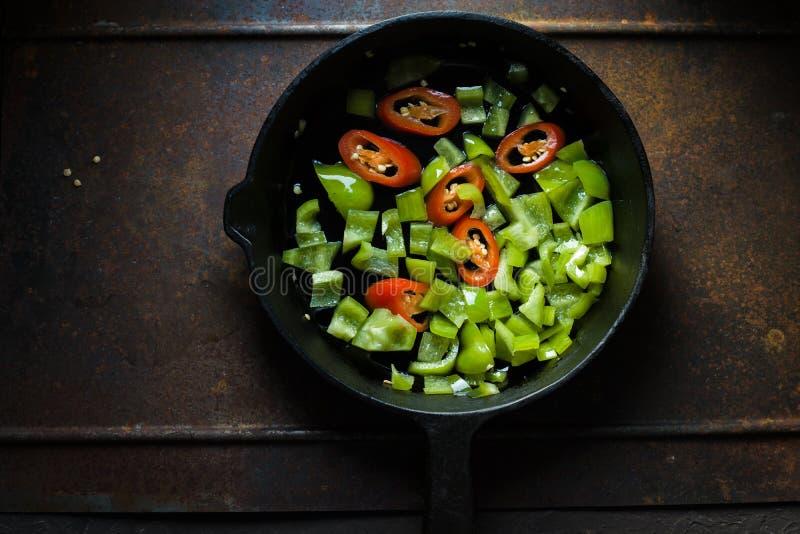 Zielony pieprz i chili na żeliwnej smaży niecki kopii przestrzeni zdjęcie stock