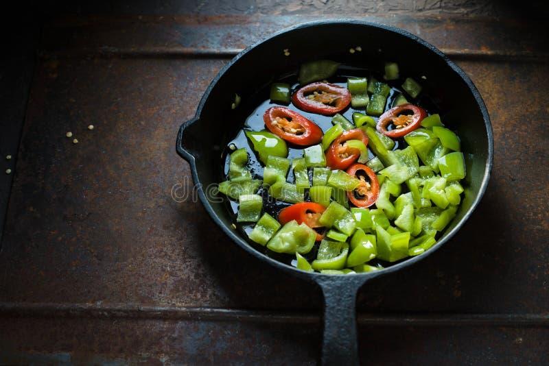 Zielony pieprz i chili na żeliwnym smaży niecka bocznym widoku zdjęcie royalty free