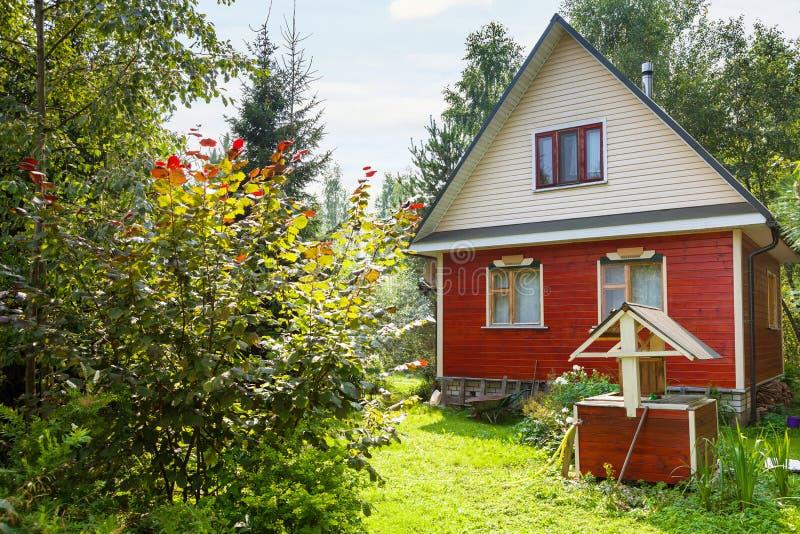 Zielony podwórko kraj chałupa z well zdjęcie royalty free