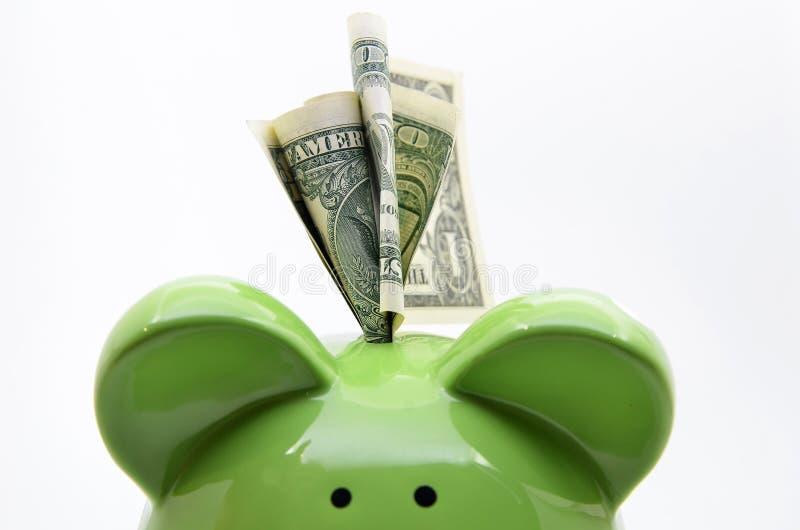Zielony prosiątko bank z dolarów amerykańskich rachunkami obraz stock